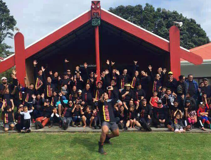 Large happy multi-generational Maori family reunion at their marae, with both children and adults wearing their custom black t-shirts, printed with red and yellow text on front.