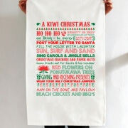"""A Kiwi Christmas"" white tea towel, with red and green Christmas text and imagery printed in rows down length of tea towel."